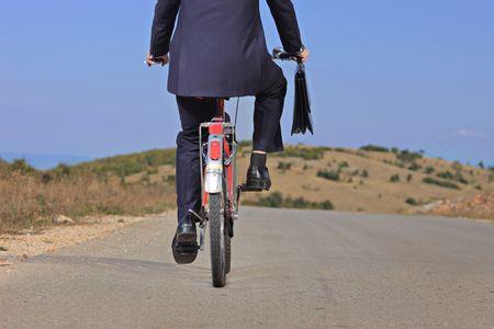 Businessman riding a bike outdoors  photo