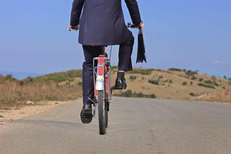 Businessman riding a bike outdoors  photo