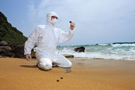 contaminacion del agua: Trabajador en un traje protector examinar la contaminaci�n en la playa