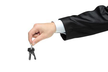 doorkey: Uomo in un vestito nero detiene le chiavi isolati su sfondo bianco