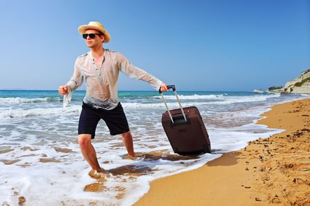 A tourist carrying a suitcase at the beach Peroulades at Corfu island, Greece photo