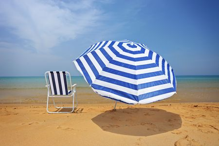 greece shoreline: A view of an umbrella and a chair on a sandy beach