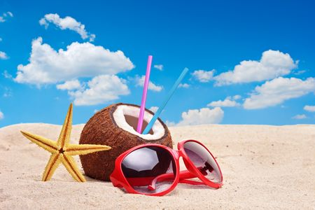A coconut, starfish and a sunglasses on a beach photo