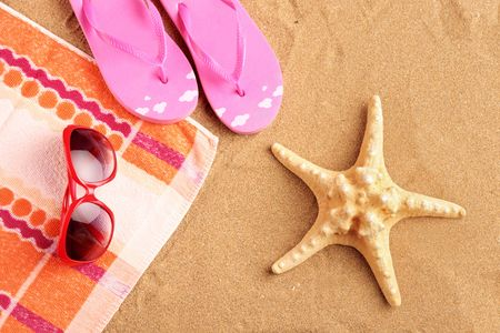 flop: Towel, sandals, sunglasses and starfish at beach Stock Photo