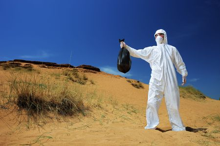 radioattivo: Un uomo in una tuta protettiva detiene un sacchetto dei rifiuti