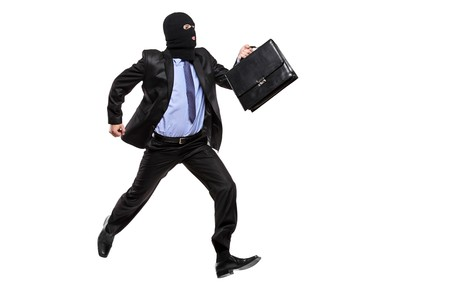 A burglar with robbery mask running away isolated on white background photo