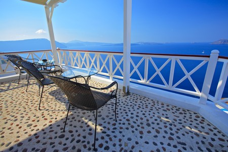 santorini: A relaxing chairs on terrace and view at Santorini island, Greece