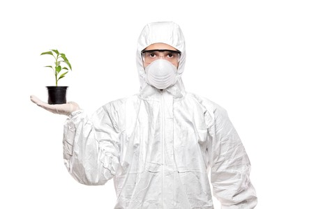 protective suit: A man in uniform holding a plant isolated on white background