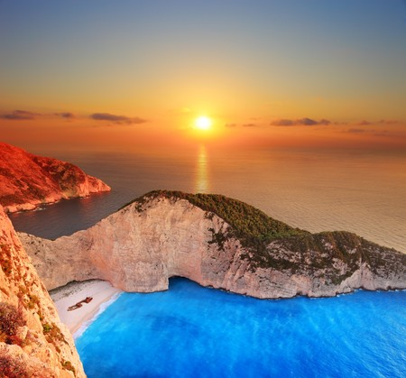 shipwreck: A panorama of sunset over Zakynthos island with a shipwreck on the sandy beach Stock Photo