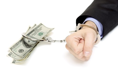 cuff bracelet: Hand with hadcuffs and US dollars isolated against white background Stock Photo