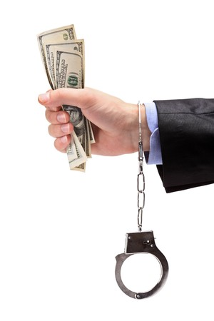 venality: Hand with handcuffs holding US dollars against white background