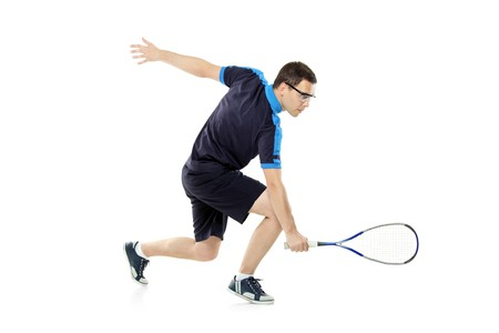squash: A squash player playing against white background