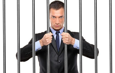 prisoner man: A businessman in jail holding bars isolated on white