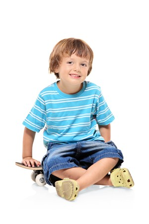 Adorable young boy sitting on a skateboard isolated against white background photo