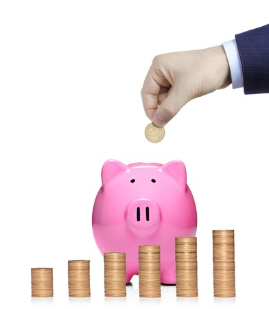 Person inserting a coin into a  pink piggy bank with stack of coins in front showing growth isolated against white background Stock Photo - 7776158