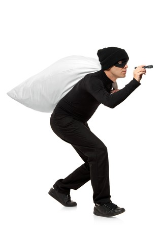 Thief carrying a bag and holding a torch isolated against white background Stock Photo - 7776148