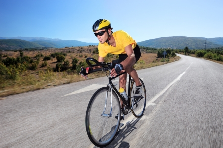 Cyclist riding a bike on an open road Stock Photo