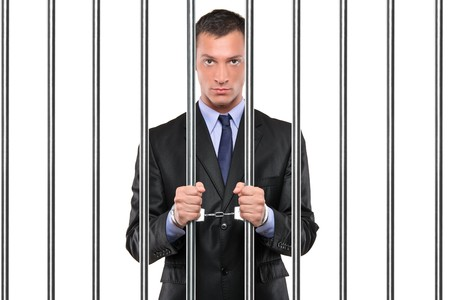 cuffed: Un empresario esposado en la c�rcel sosteniendo barras aisladas en blanco  Foto de archivo