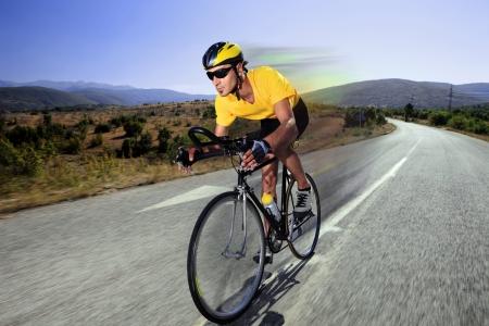 jinete: Un ciclista por manejar una bicicleta en un camino abierto en Macedonia  Foto de archivo