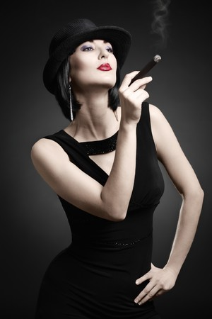 smoking cigar: A vintage woman smoking a cigar isolated on dark background Stock Photo