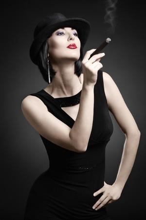 cigarro: Una mujer vintage fumar un cigarro aislado sobre fondo oscuro