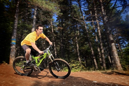 bicycle race: A young man riding a mountain bike downhill style