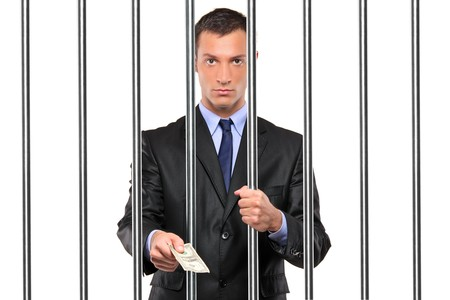 jail background: A businessman in jail giving bribe isolated on white background