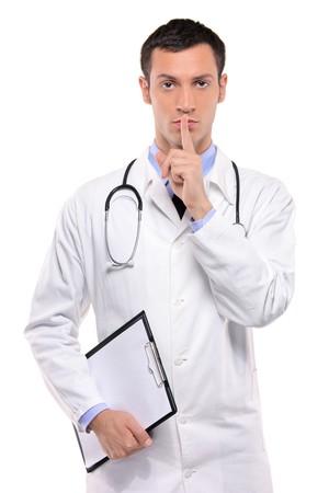 quiet adult: Un silenzio gesticolano handsome medico con il dito sulla sua bocca isolato su sfondo bianco
