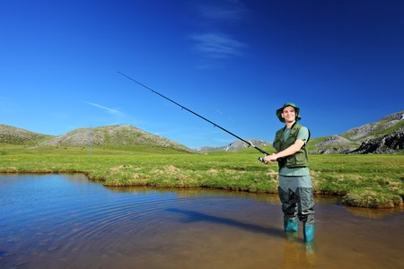fishing catches: A view of a fisherman fishing at lake with mountains the background
