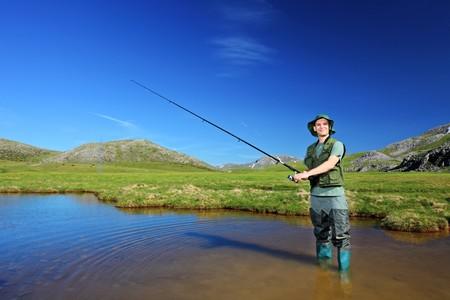 pescador: Una vista de un pescador que se pesca en el lago con montañas al fondo