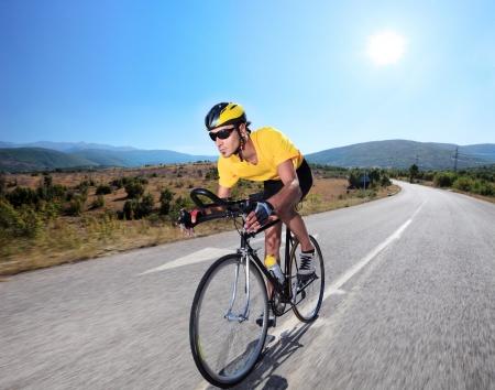 andando en bicicleta: Ciclista por manejar una bicicleta en un camino abierto  Foto de archivo
