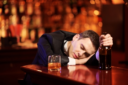 woebegone: Young drunk man sleeping in the bar, with glass of whiskey in his hand
