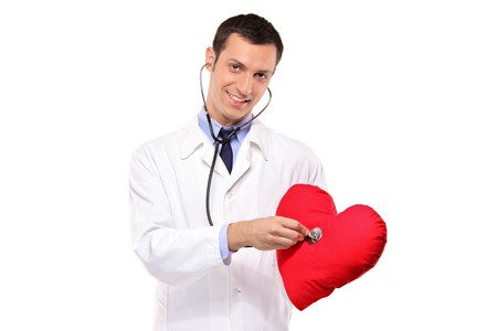 A male doctor examining a red heart shaped pillow with a stethoscope against white background photo