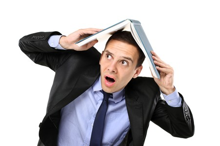 A scared young man in a suit covering his head with an open book isolated on white background photo