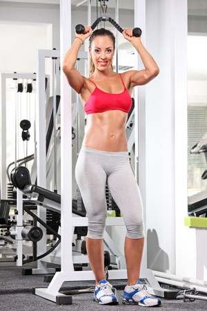 A full length portrait of a woman working out on a fitness equipment at the gym photo
