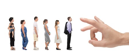 Full length portrait of men and women standing together in a line with a hand about to push them isolated against white background photo