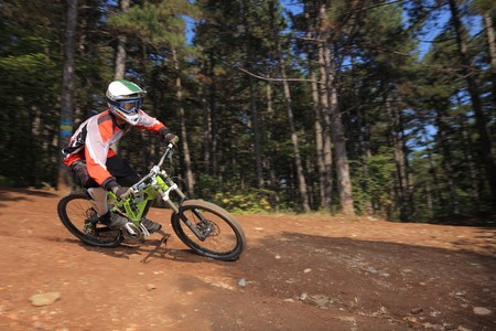 A young man with a helmet riding a mountain bike on a forest trail photo