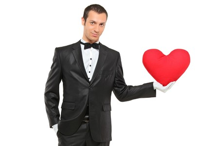 Man holding a red heart-shaped pillow isolated against white background photo