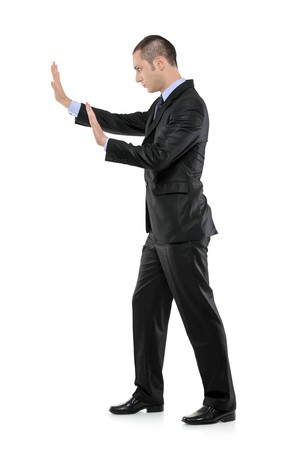 Full length portrait of a businessman pushing something imaginary isolated on white background photo