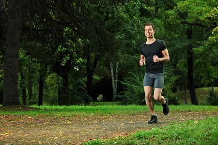 Male athlete jogging on a trail in the park photo