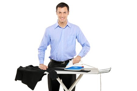 Happy young man ironing his clothes isolated against white background photo