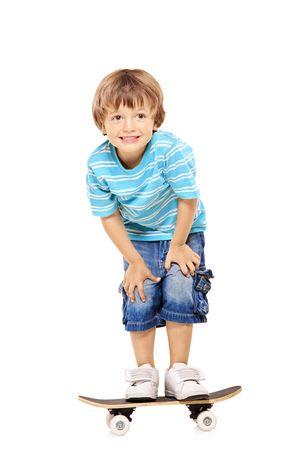 schaatsen: Volledige lengte portret van een schattige jonge jongen rijden een skateboard geïsoleerd tegen witte achtergrond Stockfoto