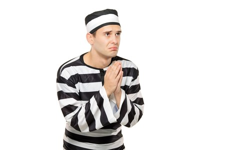 to implore: A sad prisoner with both hands clasp in begging gesture against white background