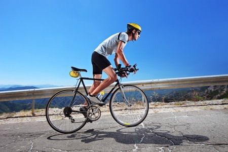 cycling race: A male cyclist riding a bike uphill along a road; clear summer day