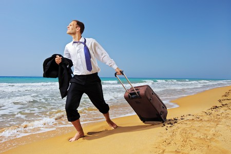 Full length portrait of a lost businessman carrying a suitcase at the beach Stock Photo - 8038082