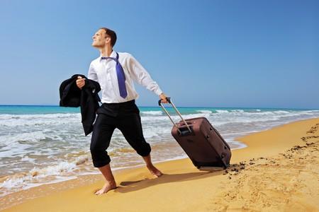 persona viajando: Retrato de longitud completa de un hombre de negocios perdido, llevando una maleta en la playa