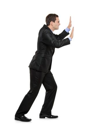 Full length portrait of a businessman pushing something imaginary isolated on white background photo
