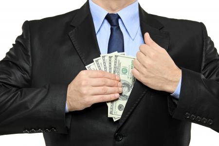earn: Un hombre de negocios con un traje negro de poner dinero en el bolsillo aislado sobre fondo blanco