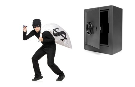 Full length portrait of a thief stealing a money bag from a deposit safe isolated on white background Stock Photo - 8100094