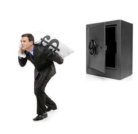 Full length portrait of a businessman stealing a money bag from a deposit safe isolated on white background photo